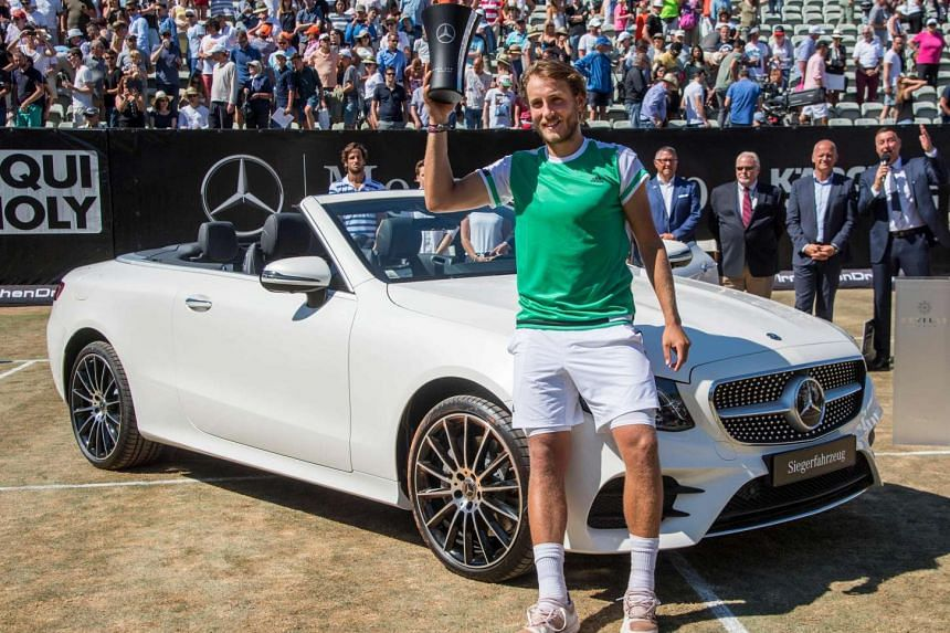 France's Lucas Pouille posing next to the winner's car, a Mercedes-Benz E400 Cabrio 4 Matic, after defeating Spain's Feliciano Lopez in the final of the ATP Mercedes Cup tennis tournament in Stuttgart on June 18, 2017.