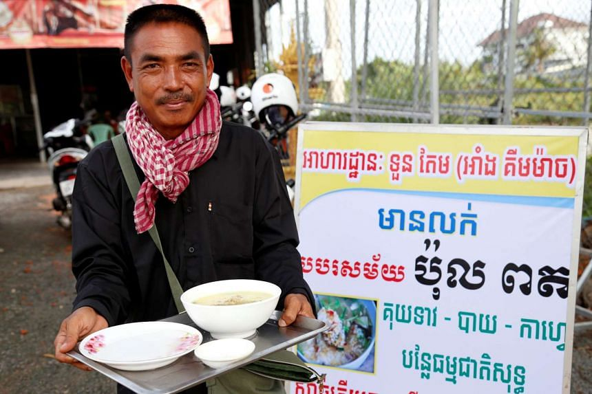 Tuon Tem, 49, holding a bowl of porridge outside his restaurant in Siem Reap province on June 19, 2017. He is offering the dish to remind Cambodians how tough life was under the Khmer Rouge.