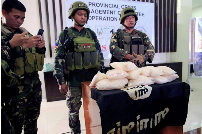 "Government forces display 11kg worth 110 to 250 million pesos ($2.2 to 5 million USD) of high grade Methamphetamine Hydrochloride ""Shabu"" and the ISIS flag recovered by troops from the Maute group in a conflict area in Marawi City on June 19, 2017."