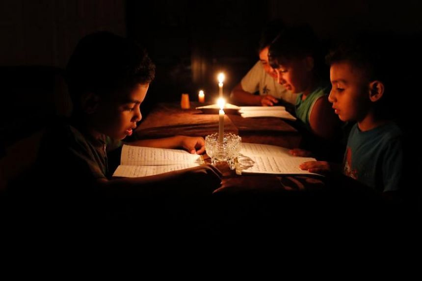 Palestinian children at home reading books by candle light due to electricity shortages in Gaza City, on June 13, 2017.