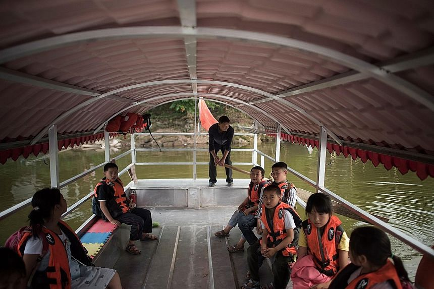 Mr Li Congshu ferrying his pupils after school in Dazu district in south-west China's Chongqing municipality. He has been transporting pupils to and from school for more than 20 years. The crossing of the Xiangshuitan reservoir by boat takes about ha
