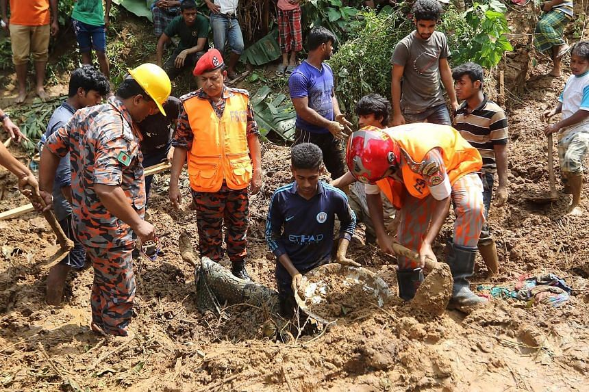 Bangladeshi firefighters recovering a body after a landslide in Rangamati last week. Bangladesh was hit by the worst mudslides on record last week, killing 158.