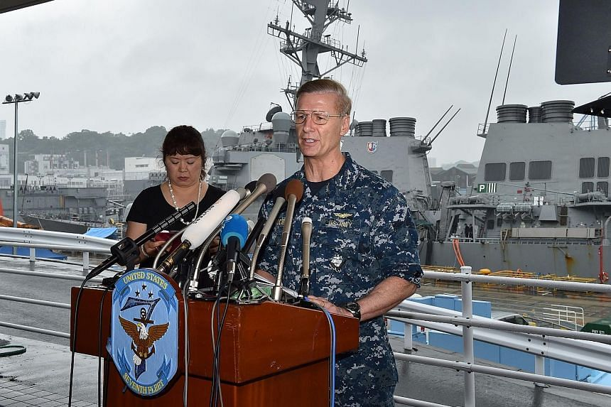 """US Seventh Fleet commander Joseph Aucoin in front of the USS Fitzgerald at the US Navy base in Yokosuka, Japan, yesterday. The navy said it had found """"a number"""" of bodies inside the warship, but did not specify if all seven missing crew members had b"""