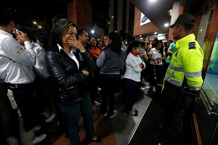 A crowd stand outside the Andino Mall in Bogota on Saturday after an explosive device went off in a restroom. The shopping centre is in an affluent area of the capital that is popular with foreigners.