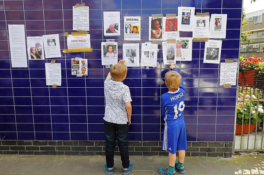 Posters of missing people after the Grenfell fire on display on a wall in Kensington on Saturday. Prime Minister Theresa May is facing pressure for keeping a distance from residents while visiting the site last week.