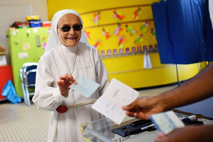 A Catholic nun voting at a polling station in Nantes, western France, yesterday. About half of REM's candidates are newcomers to politics, drawn from diverse fields of academia, business or local activism.