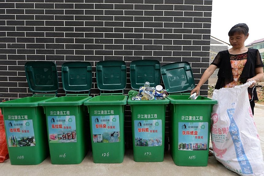 A worker sorting out garbage in a village in China's Jiangxi province. Efforts to encourage recycling and waste-sorting have not been able to keep up with the rising consumption by the country's expanding middle class over the past decade. China is n