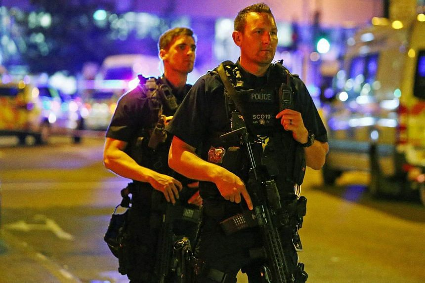 Armed police officers attend to the scene after a vehicle collided with pedestrians in the Finsbury Park neighborhood of North London, Britain ON June 19, 2017.