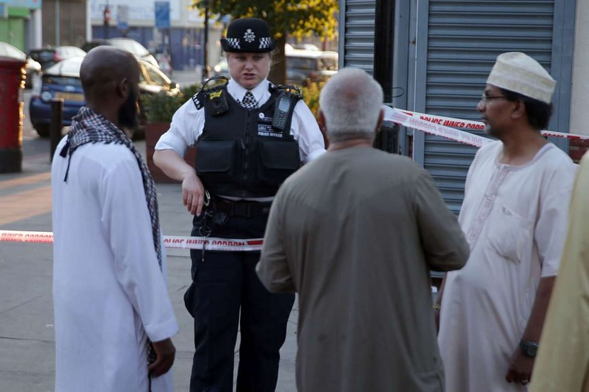 A police officer talks with residents in the Finsbury Park area of north London after a vehicle hit pedestrians, on June 19, 2017.