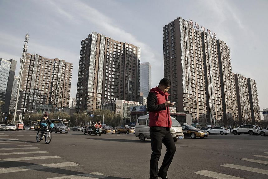 A pedestrian uses a smartphone while crossing a road in front of residential buildings in Beijing.