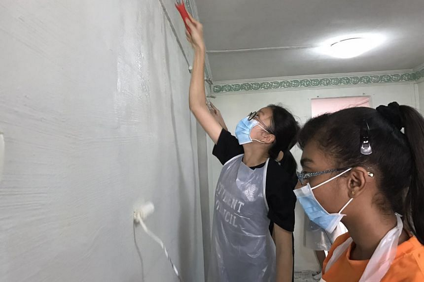 Students at one of the beneficiary's apartment at Blk 249, giving the interior a fresh coat of paint.