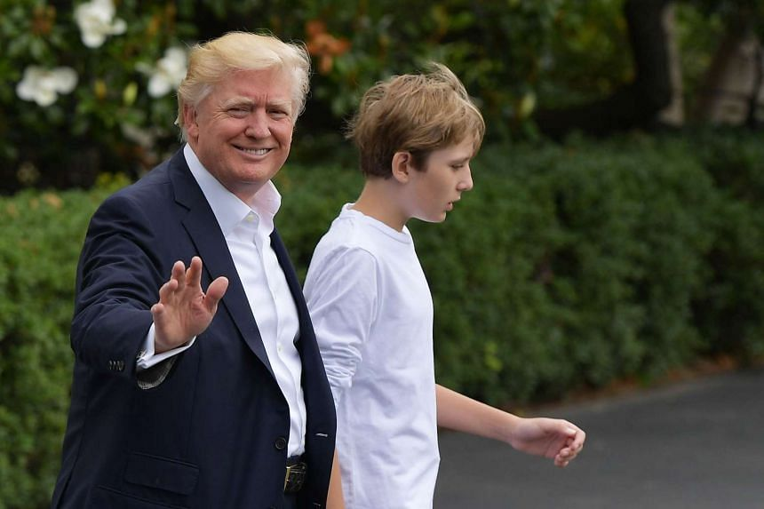US President Donald Trump and son Barron walk on the South Lawn of the White House on June 17, 2017.
