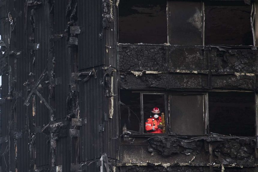 A fireman looks out from the remains of Grenfell Tower, a 24-storey apartment block in London, Britain, on June 18 2017.