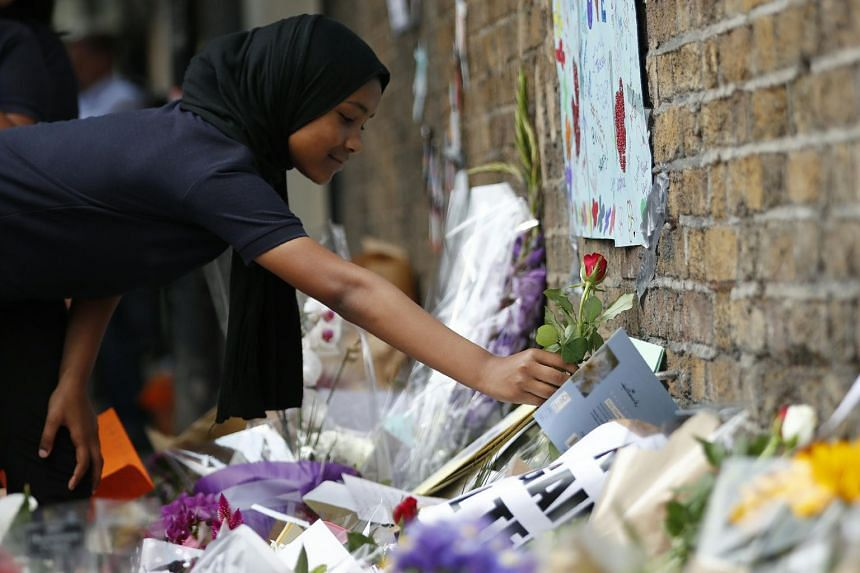 Children from Pakeman Primary School arrive to lay flowers in tribute to the victims of a June 19 van attack in the Finsbury Park area of north London, on June 20, 2017.