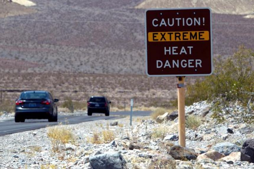 A sign warns of extreme heat as tourists enter Death Valley National Park in California.