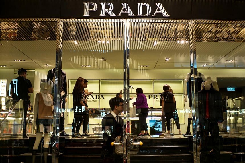 An employee stands at the door as customers browse merchandise inside a Prada SpA luxury fashion store in Hong Kong.