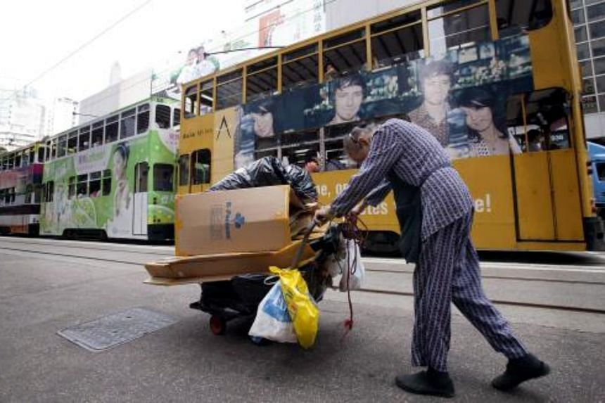 File photo of an elderly woman pushing a trolley load of cardboard for recycling through a market in the Wanchai district of Hong Kong.