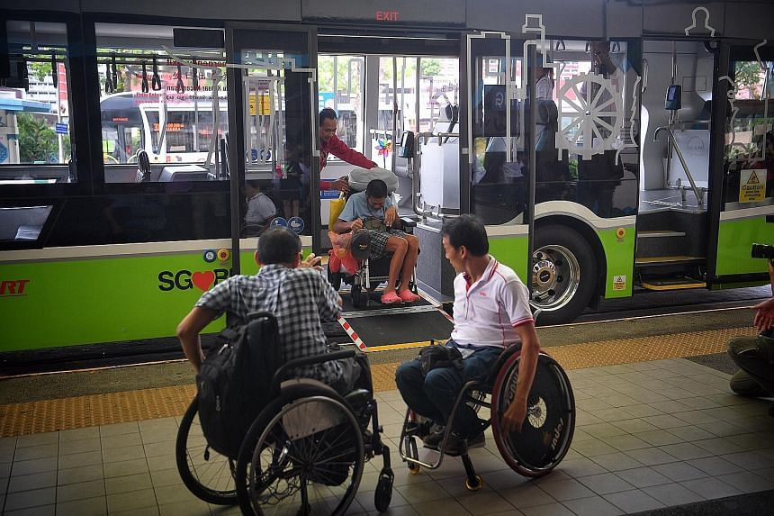 Members of the Handicaps Welfare Association trying out the wheelchair ramp on the new three-door single-deck bus at Choa Chu Kang bus interchange yesterday.
