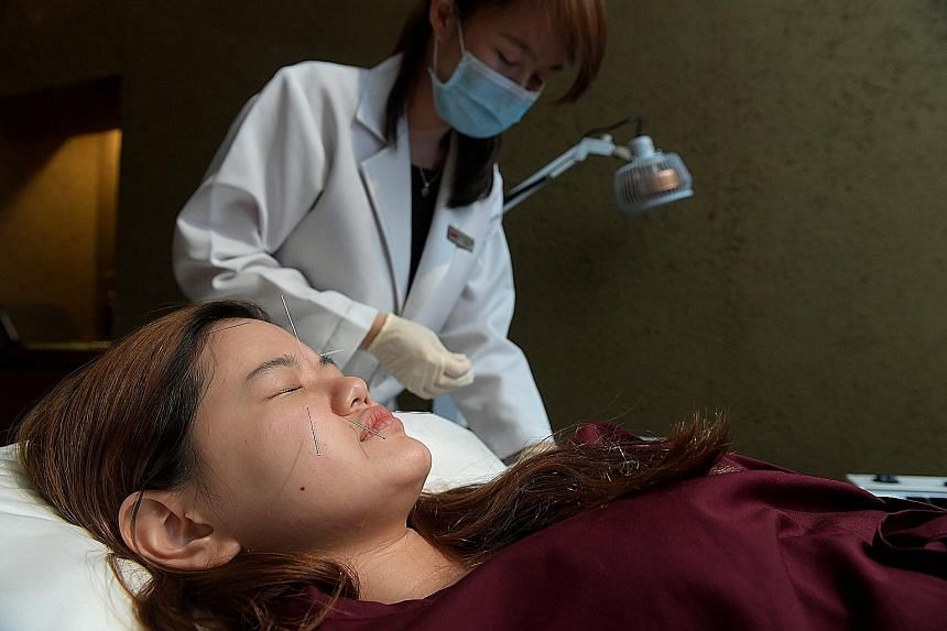 Reporter Prisca Ang, being given facial acupuncture by TCM physician Anita Pee, found it slightly ticklish but relatively painless.