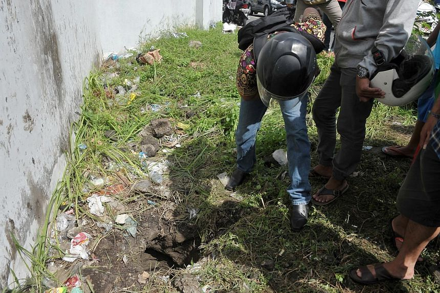 People looking into a hole outside Kerobokan Prison in Denpasar, Bali, yesterday. Four inmates made an audacious breakout via a 12m-long tunnel measuring 50cm by 75cm in cross section, Bali police said yesterday. The escape came just days after dozen