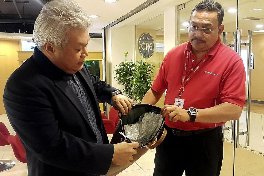 Sunway Malls' chief operating officer Kevin Tan (left) and security manager Adnan Adil Ariffin with one of the foil-lined bags used by a shoplifter.