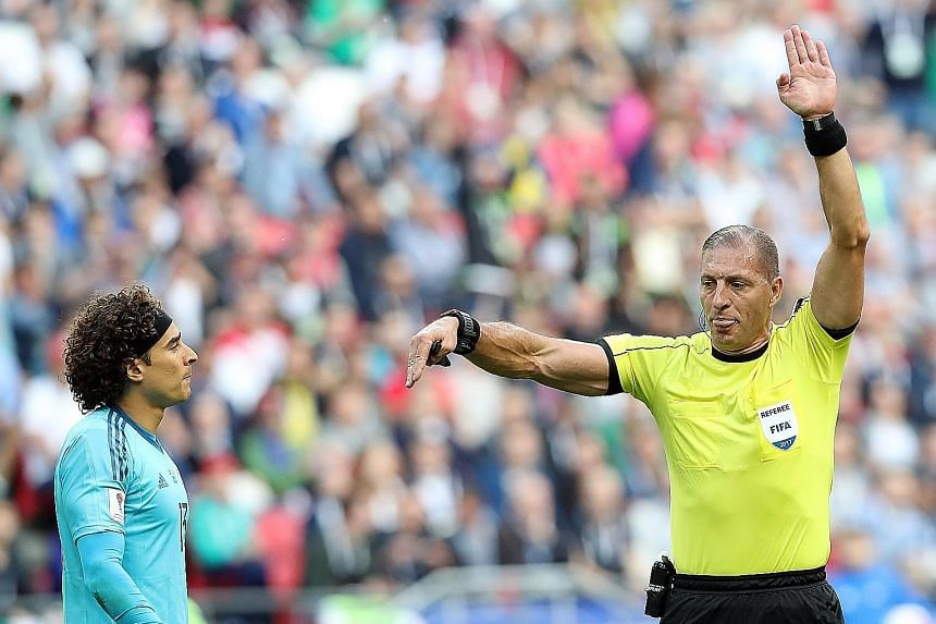 Referee Nestor Pitana relays instructions from the video assistant referee (VAR) to disallow a goal by Portugal due to offside in the Confederations Cup Group A match against Mexico in Kazan, Russia on Sunday.