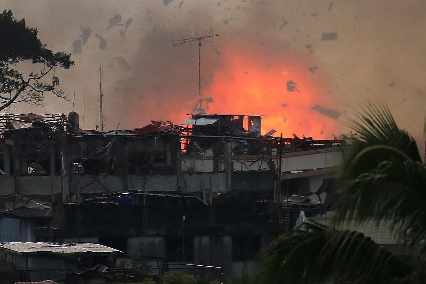 Above: Debris is sent flying into the air after a bomb explodes in Marawi City after an air strike by an OV-10 Bronco aircraft yesterday, as government forces continued their assault against Muslim militants. More than a hundred gunmen from militant