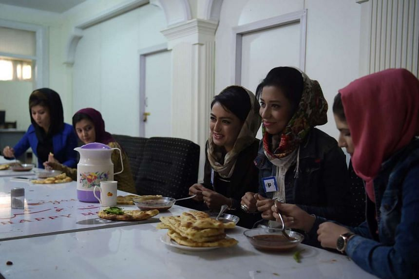 Staff having their lunch at the Zan TV (Women's TV) station in Kabul on May 24, 2017.