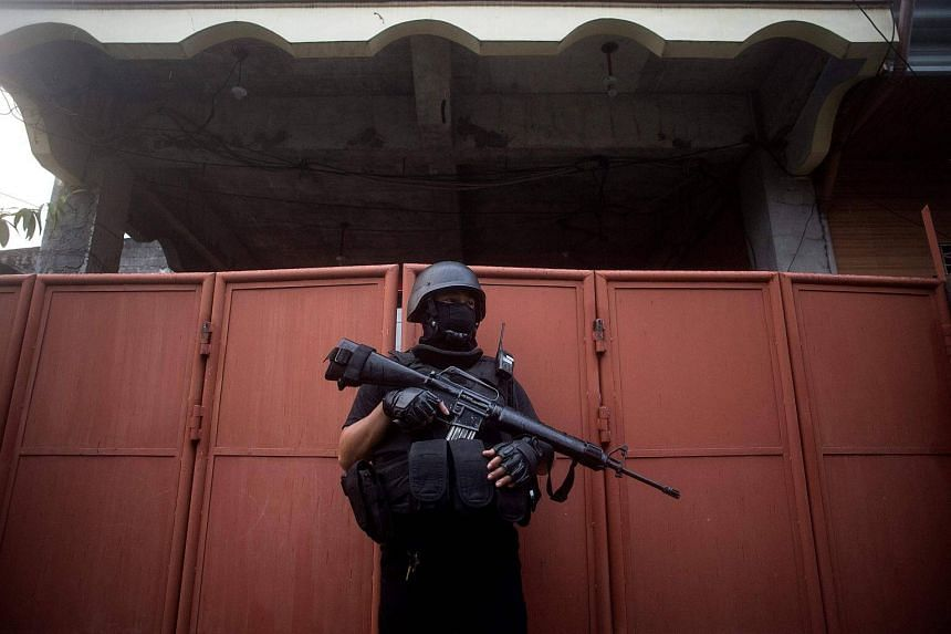 Philippine members of Special Weapons and Tactics (SWAT) patrol a neighborhood.