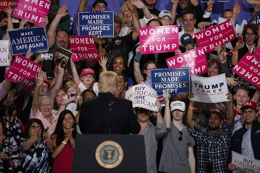 "US President Donald Trump acknowledges supporters during a ""Make America Great Again Rally"" at the Pennsylvania Farm Show Complex & Expo Centre."