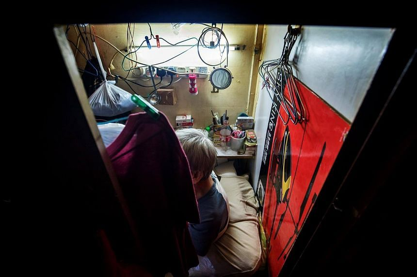 "An occupant sits inside a subdivided residential unit, known as a ""coffin home"", located inside a building in Hong Kong."