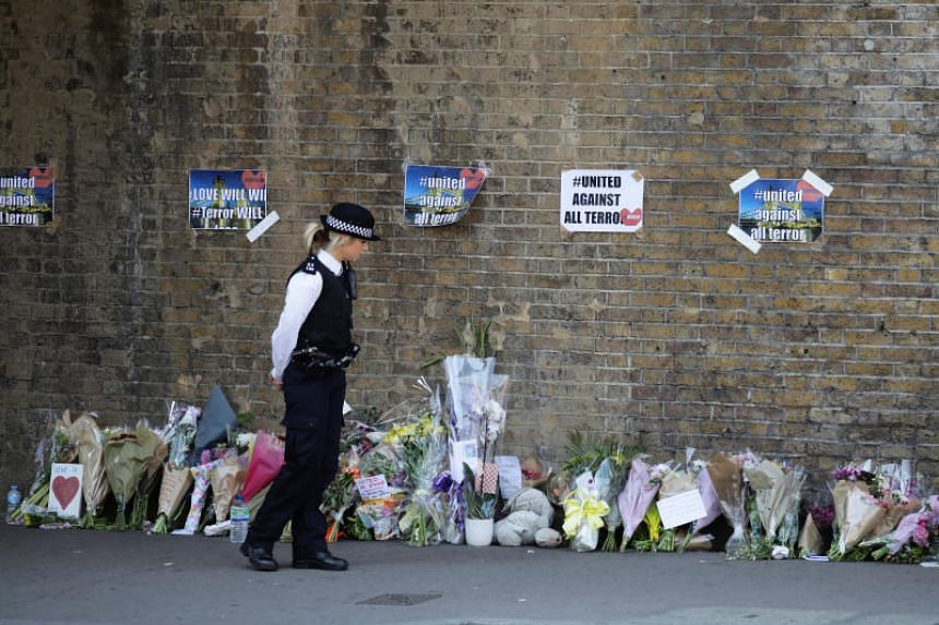 A police officer stands in front of messages and tributes left near to where a van was driven at muslims in Finsbury Park, North London, Britain on June 19, 2017.