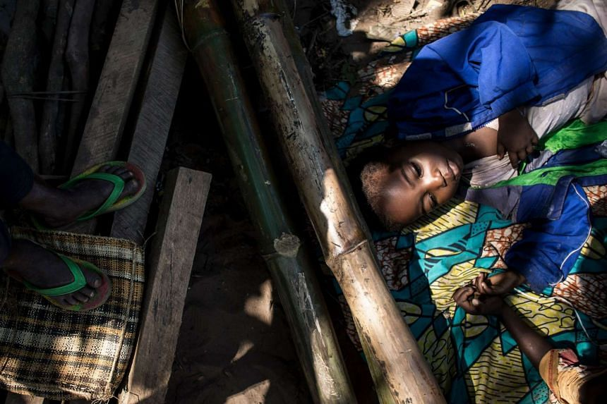 A boy rests with other displaced people fleeing conflict in the Kasai region as they wait for food rations.