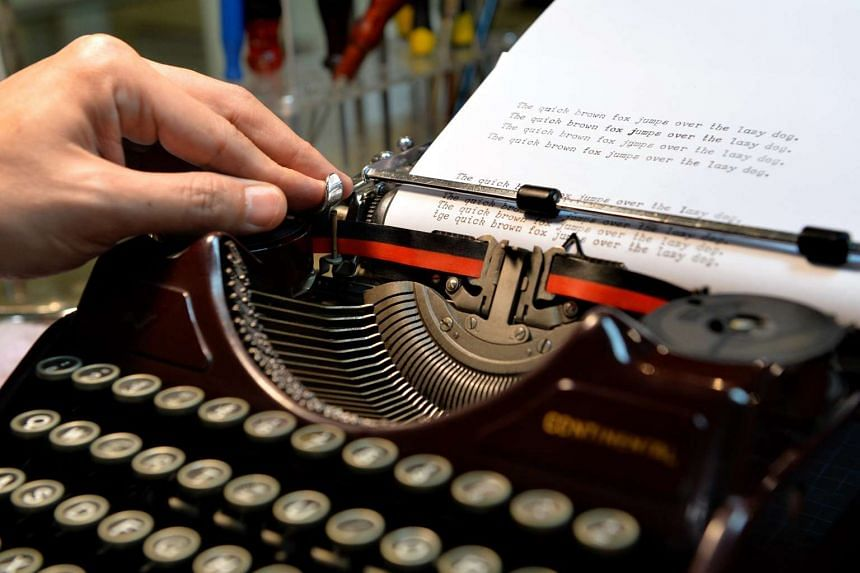 Typewriter shop owner Jason Chong pushes the paper to the side of the typewriter after completing a sentence. The former sales engineer sells and fixes old-school typewriters at his shop, Vintage Empire, at Katong Plaza. PHOTO: TNP FILE