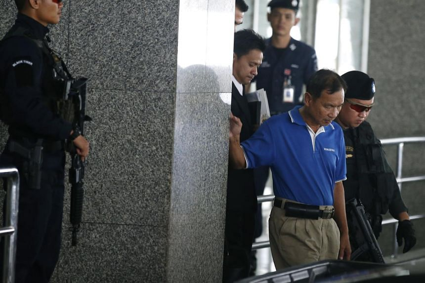 A suspect in the alleged bomb attack on the Phramongkutklao Hospital, Watana Pumret, 61, (second from right) is escorted by Thai policemen after a press conference at the Royal Thai Police Headquarters in Bangkok, Thailand on June 20, 2017.