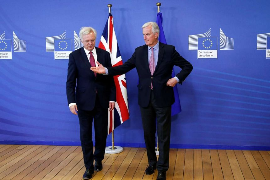 Michael Barnier (right) welcomes David Davis to their first day of talks in Brussels on June 19, 2017.