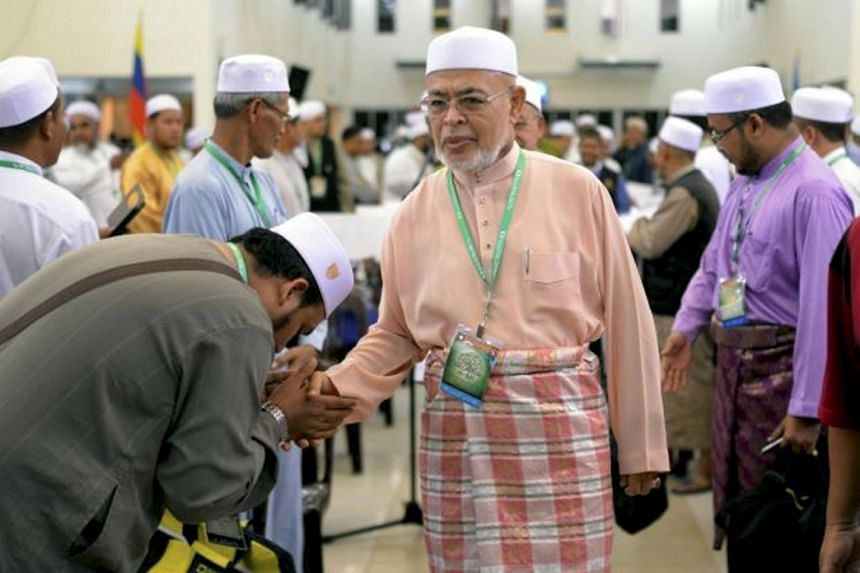 A Muslim worshipper kissing the hand of Dr Haron Din, spiritual leader of Islamist Parti Islam SeMalaysia (PAS).