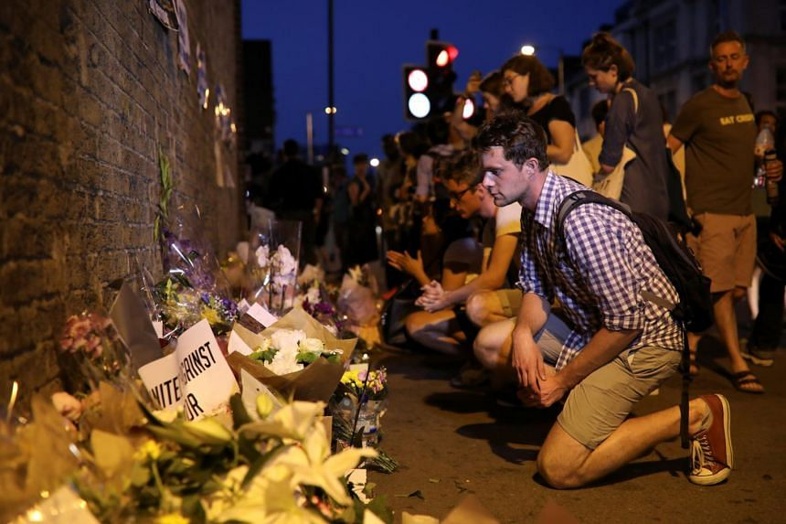 A man looks at messages and tributes left near to where a van was driven at Muslims in Finsbury Park, North London.