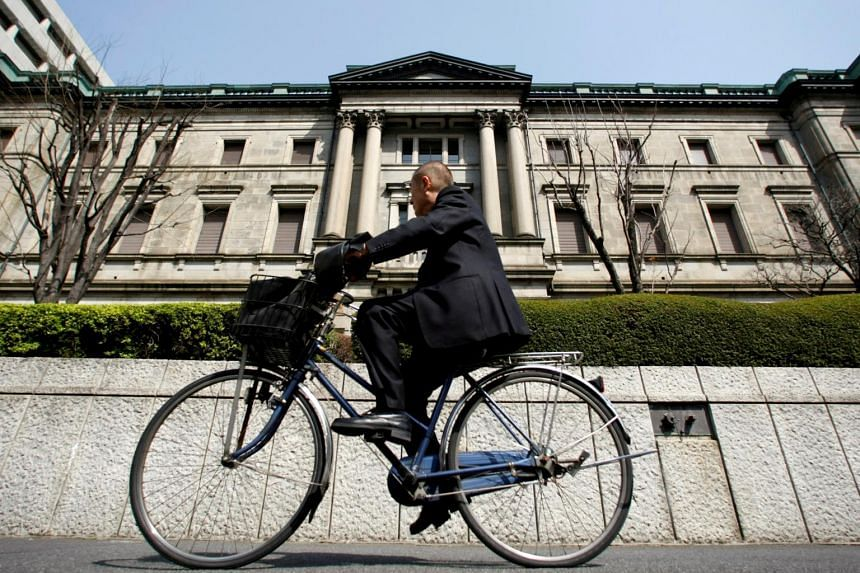A man rides a bicycle past the Bank of Japan building in Tokyo.