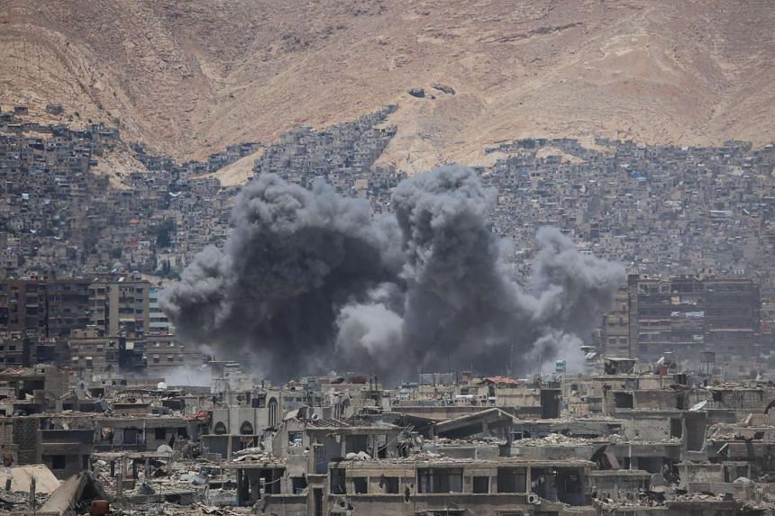 Smoke billowing from damaged buildings following a reported air strike in the rebel-held parts of the Jobar district, on the eastern outskirts of the Syrian capital Damascus, on June 18, 2017.