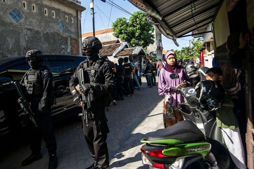 Members of the Densus 88 counter-terrorism police cordon off a road as they search a house in Surabaya, East Java province, on June 19, 2017, following the arrest of a man suspected of links with the Islamic State (IS) group.