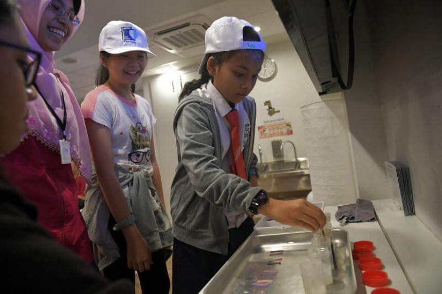 (From left) Aishah Shaaban Hashem Ibrahim Sawalim, 12, Eugenia Chew, 11, and Syifa Nisrina bte Sapian, 11, learn about the differences between alkalinity and acidity at Kidzania on June 21, 2017.