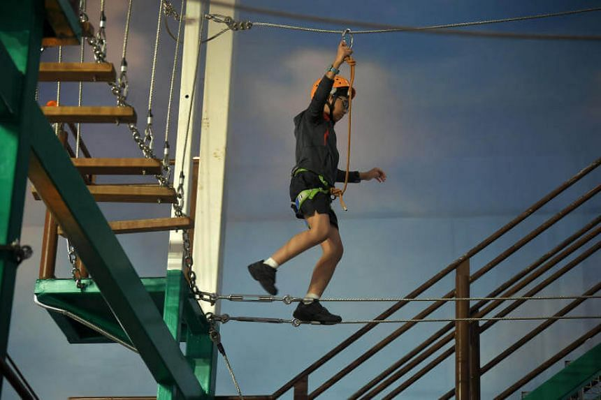 STSPMF beneficiary Gabriel Wong, 11, tries out the obstacle course at the mountaineering school at Kidzania on June 21, 2017.