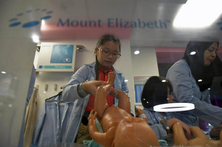 STSPMF beneficiary Fan Ming Yin, 11, tries out being a nurse looking after babies at the hospital establishment at Kidzania on June 21, 2017.
