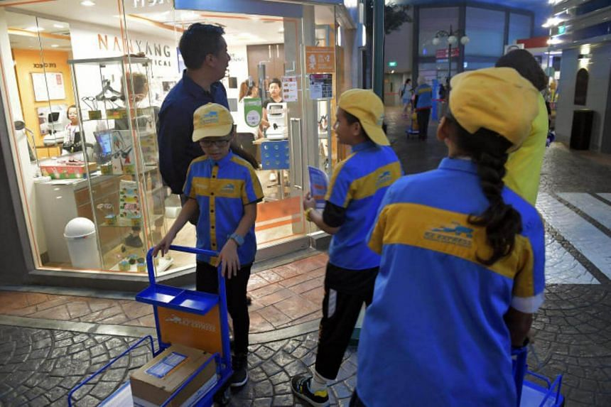 STSPMF beneficiaries Beh Ke Xuan, 10, (left) and Muhammad Aliff Mattin Bin Abdul Salim, 12, (centre) collecting parcels as couriers at Kidzania on June 21, 2017.