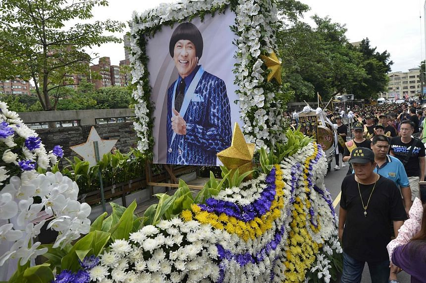 A car covered with flowers and carrying Chu Ke-liang's portrait led the huge procession, followed by lion and dragon dancers, a marching band and a dozen luxury cars.