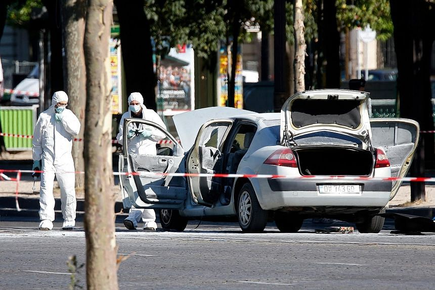 A police team inspecting Adam Djaziri's burnt car on the Champs-Elysees in Paris on Monday. The car had been loaded with two gas canisters, and two handguns and a Kalashnikov-style assault rifle were found in the vehicle.