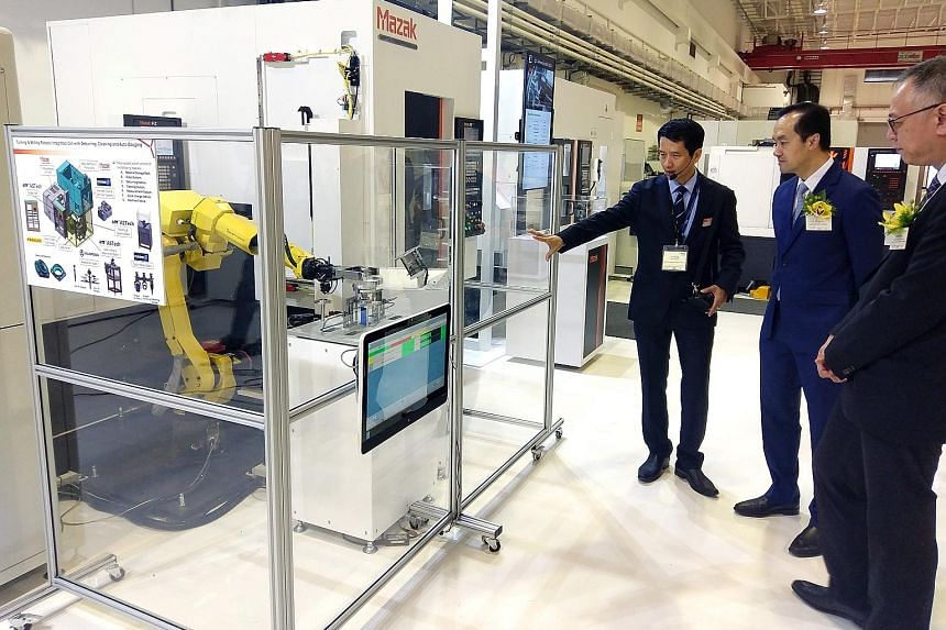 Senior Minister of State for Trade and Industry and National Development Koh Poh Koon (right) learning about the high-tech production equipment at Yamazaki Mazak's manufacturing plant in Singapore from Mr K. S. Chong, senior director, Yamazaki Mazak