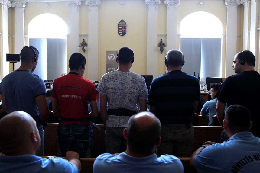 Defendants charged with causing the death of 71 migrants standing during their trial in Kecskemet, Hungary, on June 21, 2017.