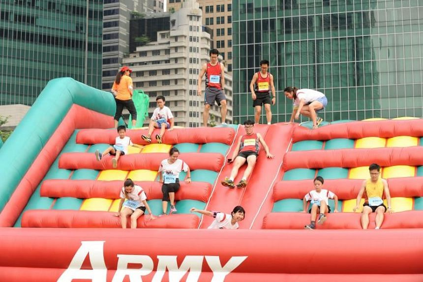 Participants manoeuvring their way through the inflatable Rubble obstacle at the Safra Singapore Bay Run & Army Half Marathon on Aug 28, 2016.